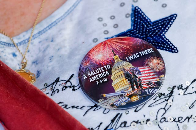 A woman wears a special button as she joins others to watch the parade