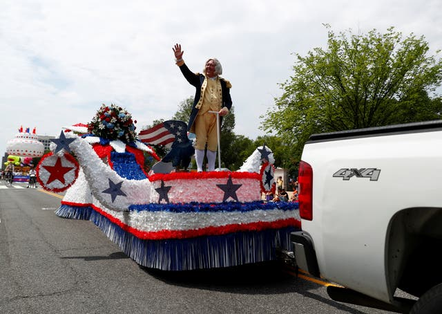 A man dressed in a historical uniform waves from a float
