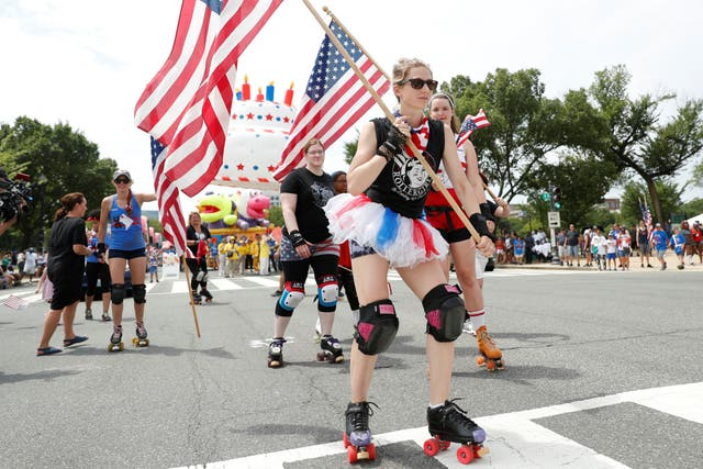 Women in roller derby outfits skate by with national flags