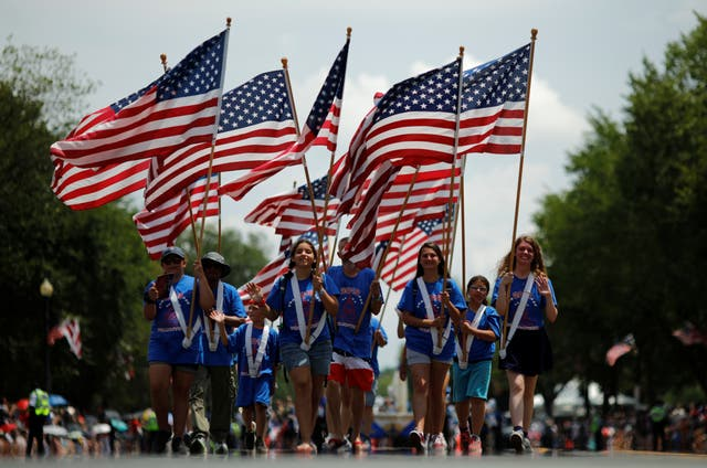 People carry U.S. flags as they take part in a parade