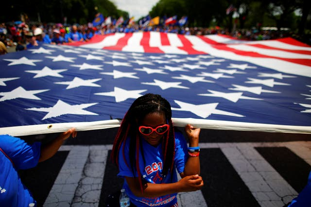 A girls helps carrying a U.S. flag as she takes part in a parade