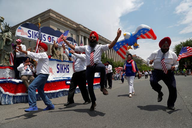 Men dance next to the Sikhs of America float