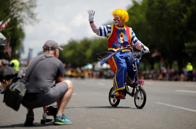 A clown passes by on a bicycle