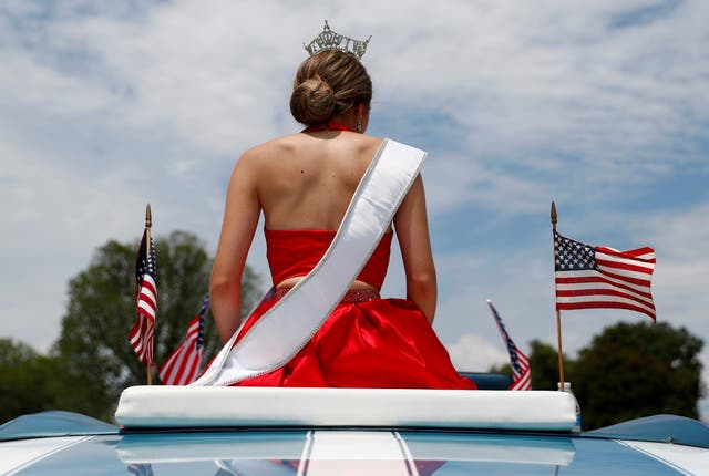 Miss Maryland, Mariela Pepin, wearing her sash and tiara, rides in an open-top vehicle