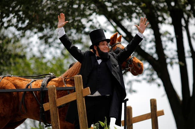 A dressed-up man gestures next to a horse