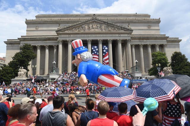 People watch the Independence Day parade as it passes in front of the National Archives