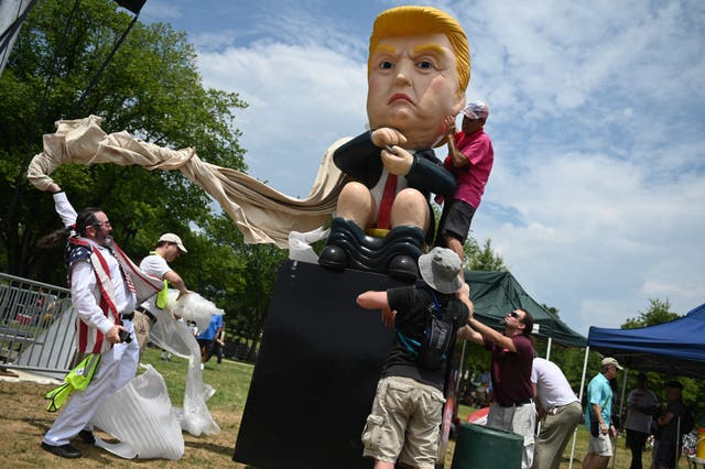 """Protesters unveil a statue of US President Donald Trump tweeting on a toilet, at the National Mall ahead of the, """"Salute to America"""" Fourth of July event with US President Donald Trump at the Lincoln Memorial in Washington, DC"""