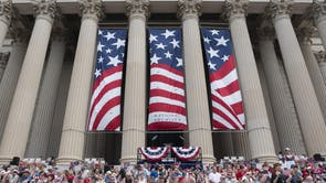 Parade-goers sit at the National Archives for the reading of the Declaration of Independence and the Independence Day Parade along Constitution Avenue