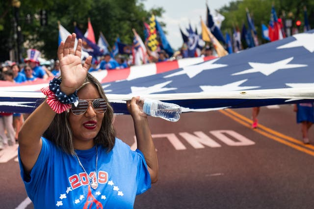 A woman waves while holding a large US flag