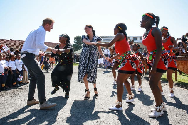 """The Duke and Duchess of Sussex dance as they arrive for a visit to the """"Justice desk"""", an NGO in the township of Nyanga in Cape Town, as they begin their tour of the region. Their first official family visit in the coastal city"""