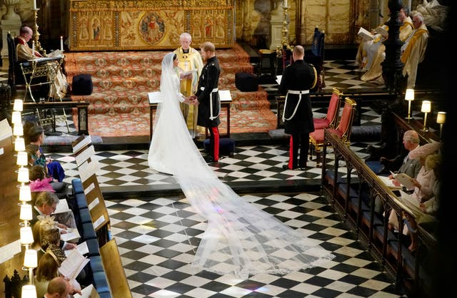 Prince Harry and Meghan Markle stand facing each other hand-in-hand before Archbishop of Canterbury Justin Welby during their wedding ceremony