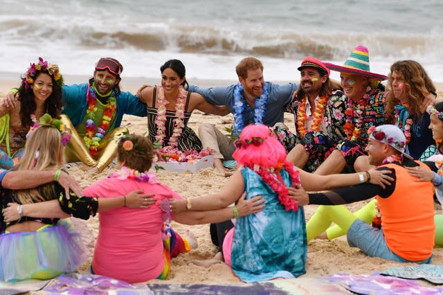 """Prince Harry and Meghan join a circle during a """"Fluro Friday"""" session run by OneWave, a local surfing community group who raise awareness for mental health and wellbeing, at Sydney's iconic Bondi Beach"""