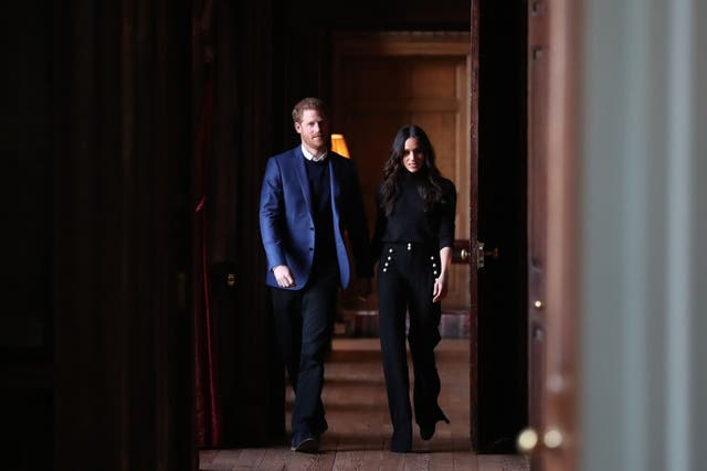 Prince Harry and Meghan Markle walk through the corridors of the Palace of Holyroodhouse on their way to a reception for young people in Edinburgh. The reception celebrated youth achievements, marking Scotlands Year of Young People 2018, an initiative that aims to inspire Scotland through its young people: celebrating their achievements, strengthening their voice on social issues and creating new opportunities for them to shine