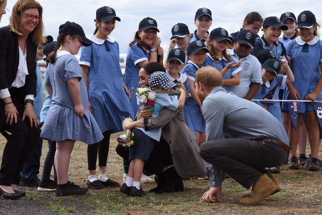 Prince Harry looks on as his wife Meghan, the Duchess of Sussex, is hugged by student Luke Vincent of Buninyong Public School following the couple's arrival at Dubbo Regional Airport in Dubbo