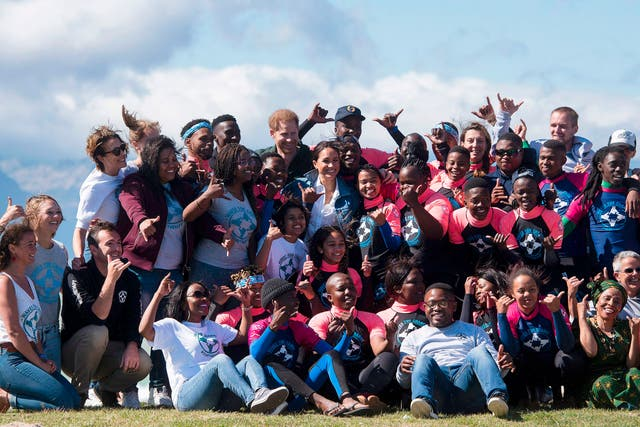 """Prince Harry and Meghan pose with members of """"Waves For Change"""" NGO at Monwabisi Beach outside of Cape Town. """"Waves For Change"""" NGO fuses surfing with child-friendly mind and body therapy to provide mental health services to vulnerable young people living in challenging communities"""