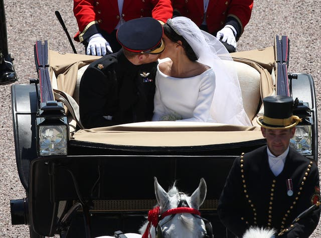 Prince Harry kisses the Duchess of Sussex, as they pass through the Cambridge Gate into the grounds of Windsor Castle at the end of their carriage procession