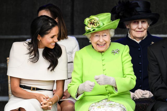 Queen Elizabeth II sitts and laughs with Meghan, Duchess of Sussex during a ceremony to open the new Mersey Gateway Bridge in the town of Widnes in Halton, Cheshire
