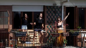 Women dance on their balcony as a radio station plays music for a flash mob to raise spirits in Rome