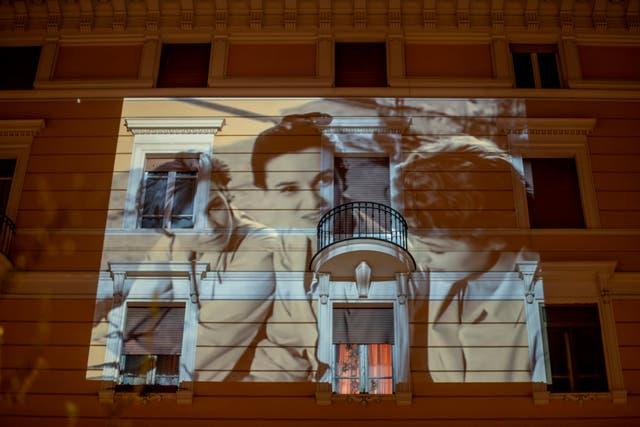 The film <i>Le ragazze di Piazza di Spagna</i> is projected on a building in Rome
