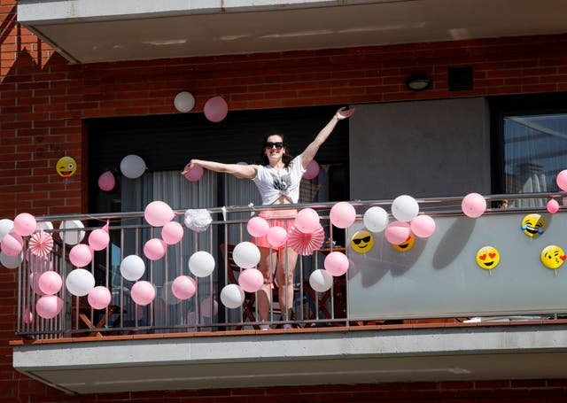 A woman gestures from her balcony in Barcelona
