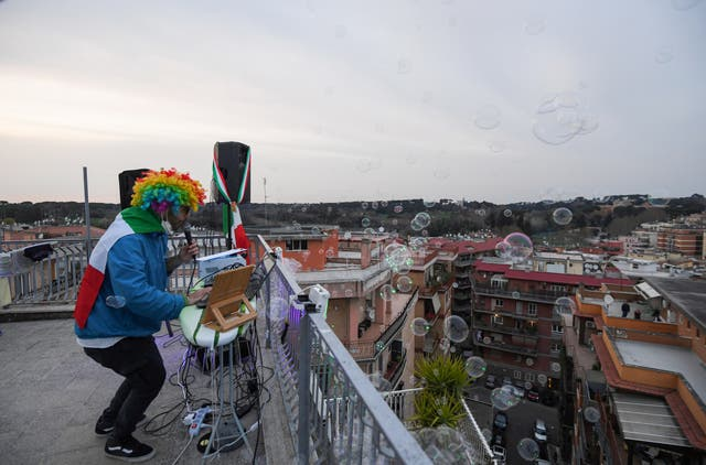 DJ Francesco Cellini plays for his neighbours from the rooftop terrace of his flat block in Rome