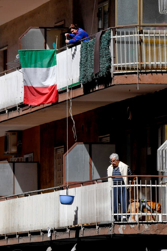 A woman uses a basket tied to a rope to pull a delivery of groceries up to her balcony in Naples, Italia