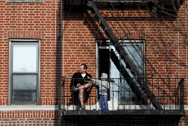 A man and his son on their balcony in Brooklyn