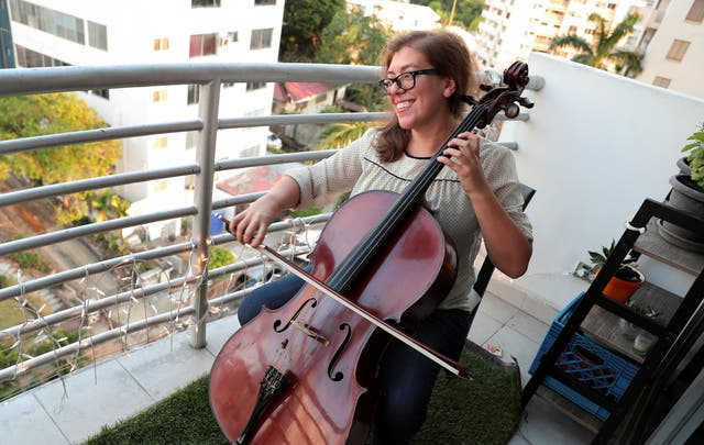 Cellist Karina Nunez performs for her neighbours at the balcony of her flat in Panama City