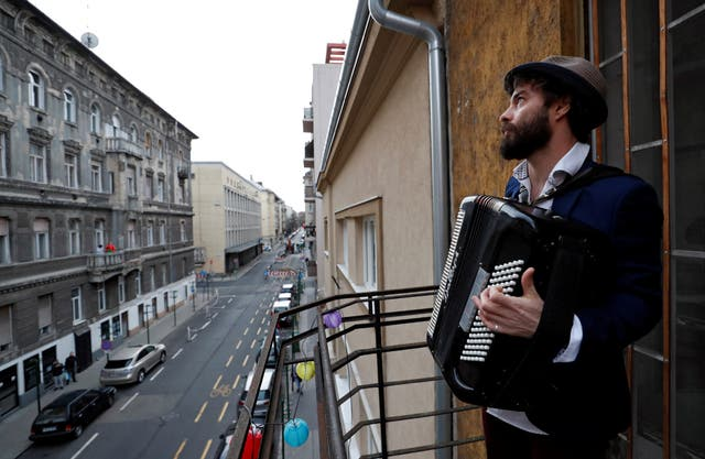Musician Adam Moser plays for neighbours from his balcony in Budapest, Ungarn