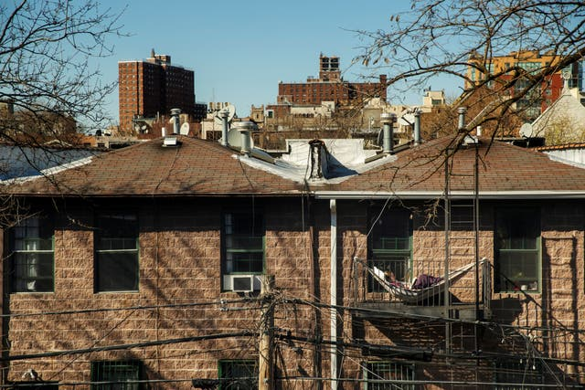 A Brooklyn resident relaxes in a hammock hung on their balcony
