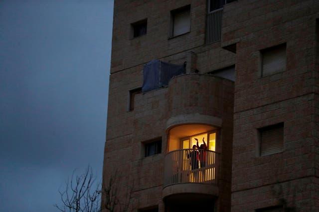 People applaud medical workers from their balconies in Modiin, Israel