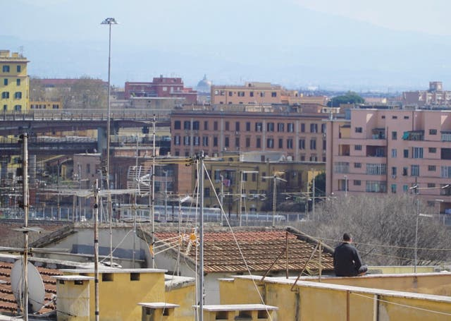 A man sits alone on a roof terrace in Rome