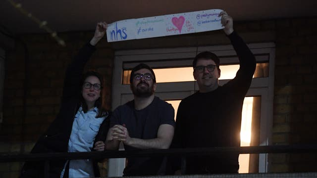 People clap from a block of flats opposite St Thomas' Hospital in London. Briton's were encouraged to clap for carers at 8pm local time to celebrate employees of the NHS