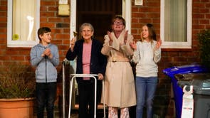 Barbara Leigh, alderen 93, (second left) rings a bell for the NHS, with her family who are all staying together throughout the lockdown, from their front garden across the road from Wythenshawe Hospital in Manchester