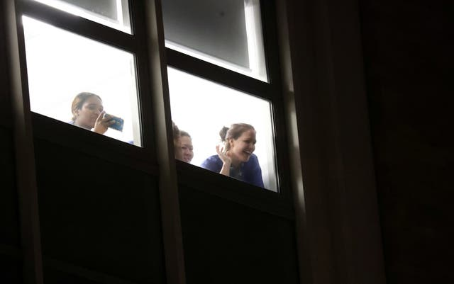 NHS workers wave from a window at Chelsea and Westminster Hospital