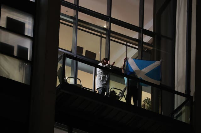People in flats wave the Scottish flag in Glasgow as they join in a national applause for the NHS