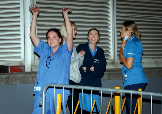 Staff outside the St James's University Hospital in Leeds, wave to people applauding them from their balconies