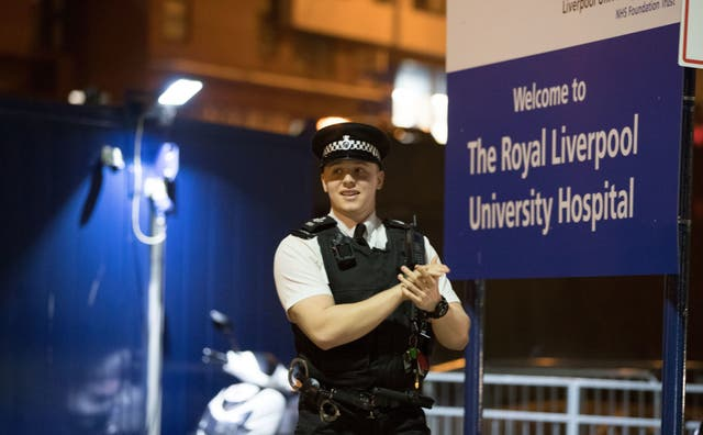 A police officer joins staff from the Royal Liverpool University Hospital in a national applause for the NHS