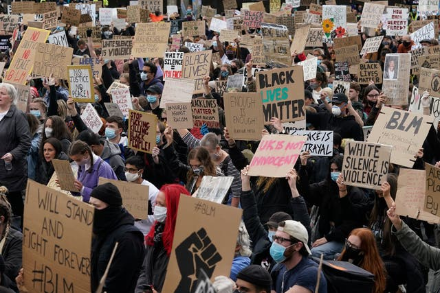 Protesters holding placards gather in Manchester