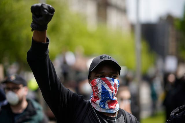 A protester raises his arm during a second day of Black Lives Matter demonstrations in Piccadilly Gardens
