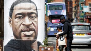 People are seen by a mural of George Floyd who died in police custody in Minneapolis, Stevenson Square, Manchester
