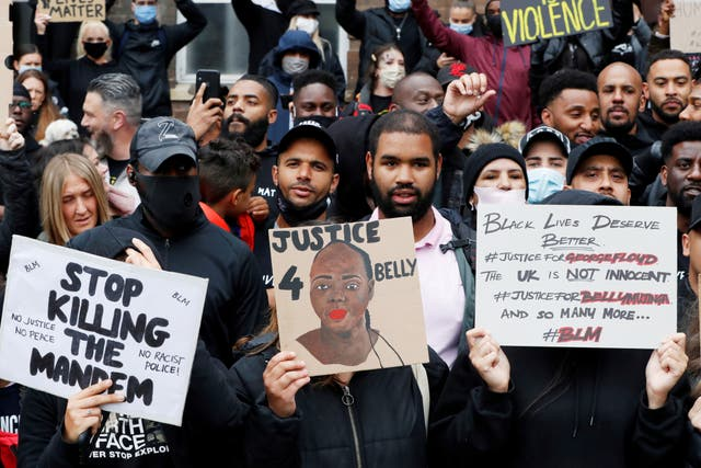 Demonstrators hold placards during a Black Lives Matter protest in Watford