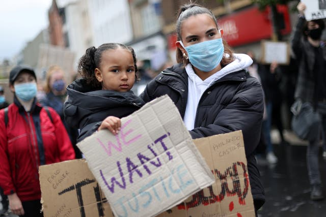 Demonstrators wearing protective face masks and face coverings hold placards during a Black Lives Matter protest in Leicester