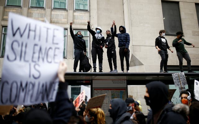 Demonstrators are seen standing on top of a bus stop wearing protective face masks and face coverings as the Black Lives Matter protesters march to the Home Office in London