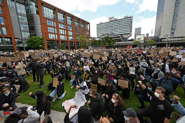 Protesters kneel as they hold placards during a demonstration in Manchester
