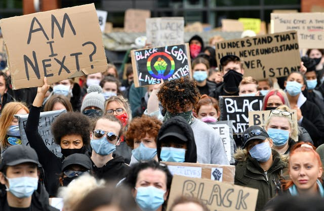 Protesters hold placards as they attend a demonstration in Manchester