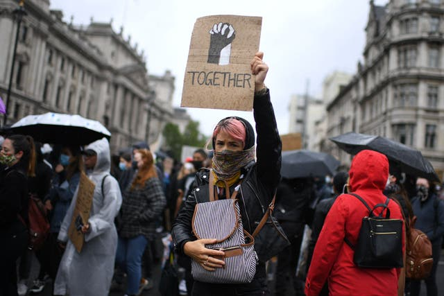 Protesters hold placards as they attend a demonstration in Parliament Square