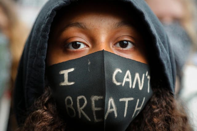 A girl wears a face mask during a Black Lives Matter rally in Parliament Square