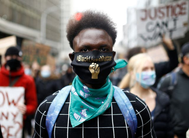 A demonstrator is seen wearing a protective face mask as the Black Lives Matter protesters march to the Home Office in London