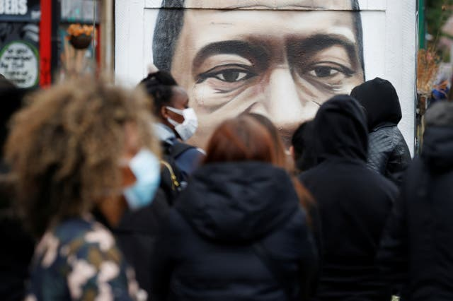 Demonstrators during a Black Lives Matter protest in Manchester are seen by a mural of George Floyd